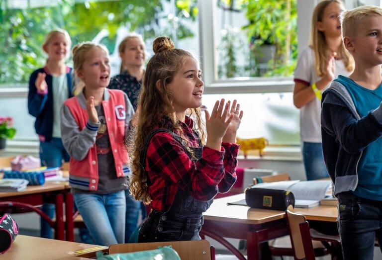 Leerkracht en leerlingen maken muziek in de klas
